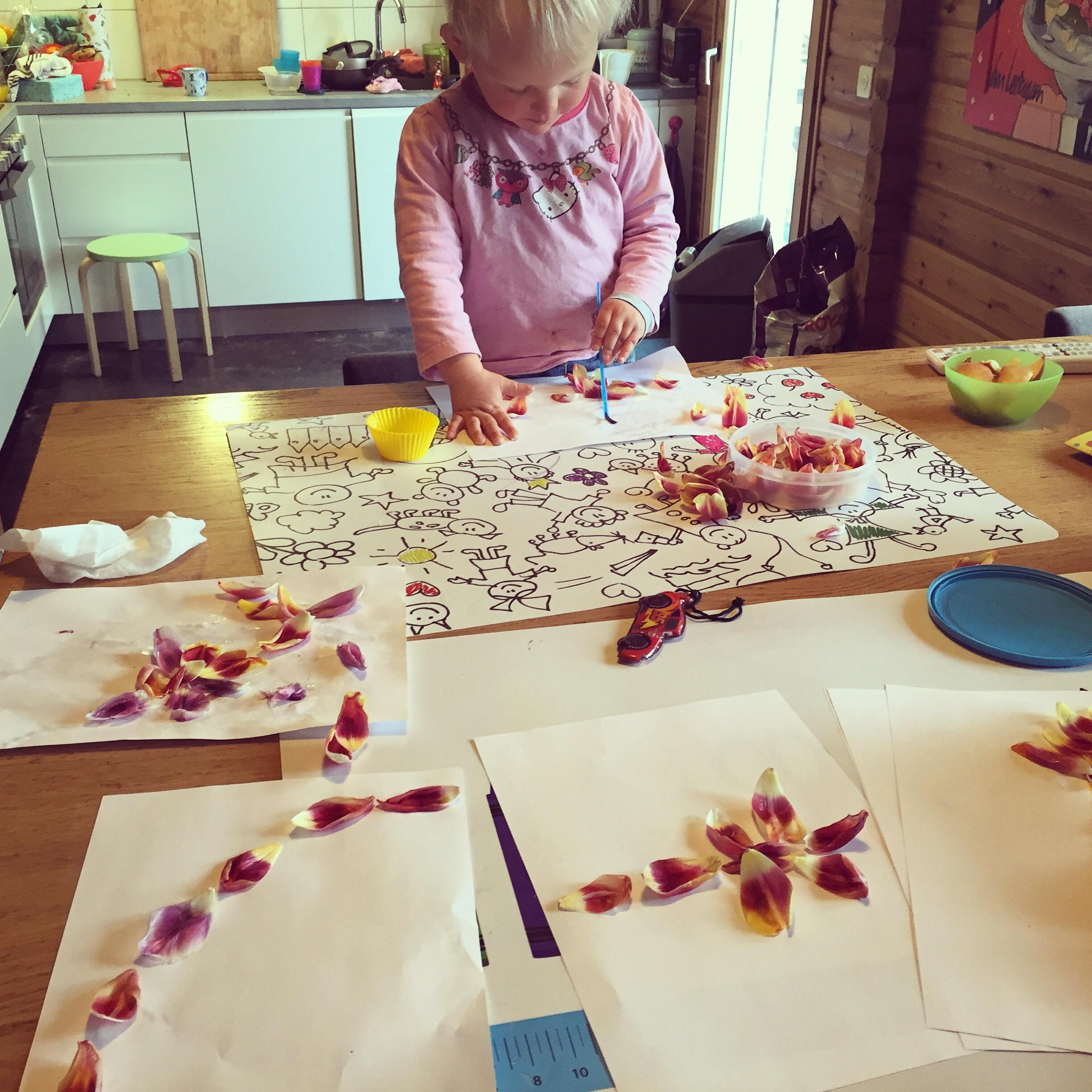 De meiden knutselen met de tulpenblaadjes.